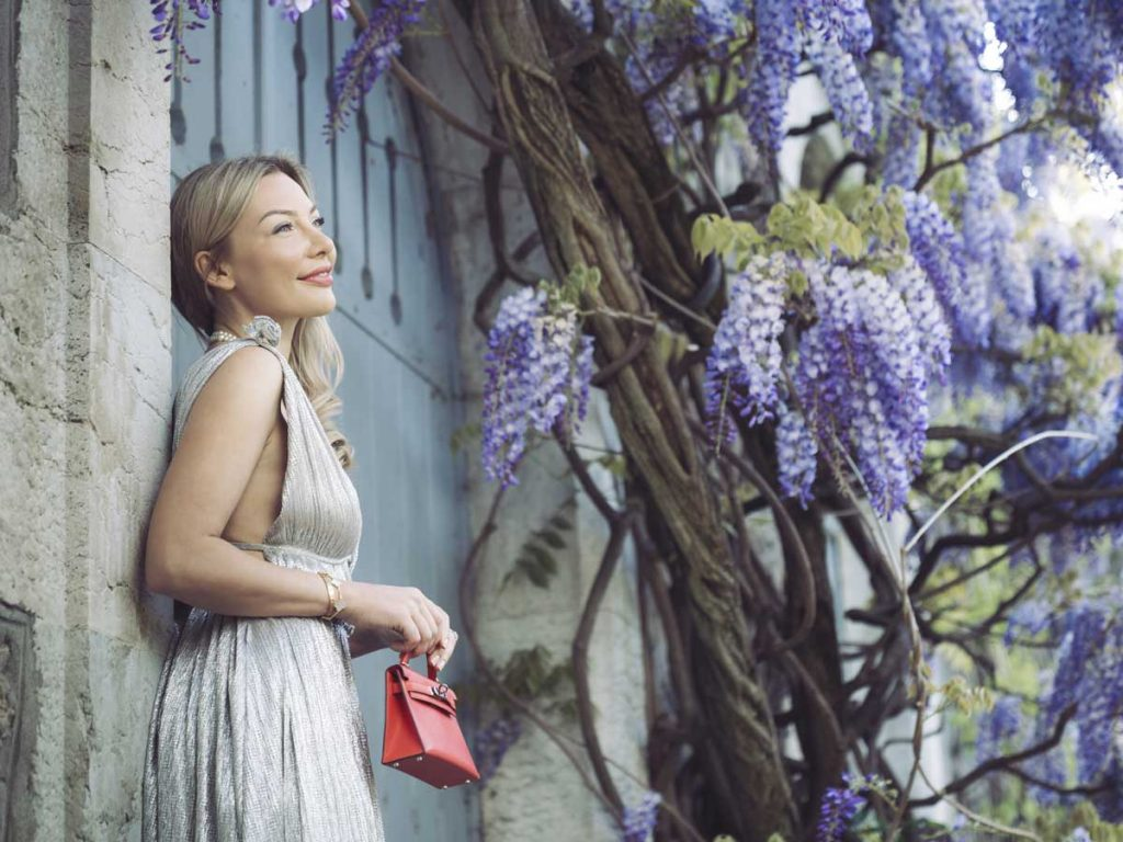 anna bey in white dress next to a flower tree