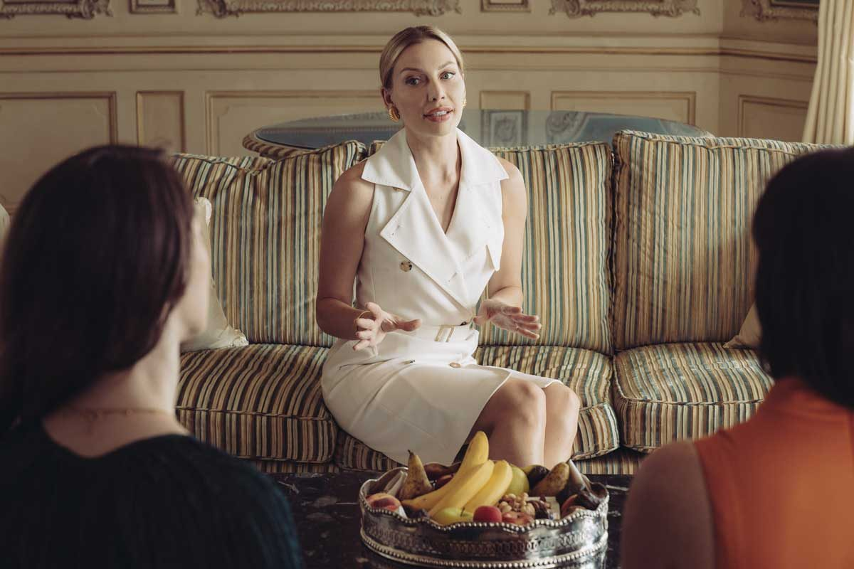anna bey sitting elegantly talking with people